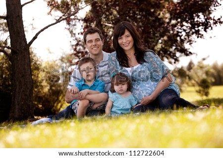 Portrait of young family in park with pregnant mother