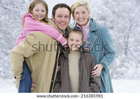 Portrait of young family in winter setting - stock photo