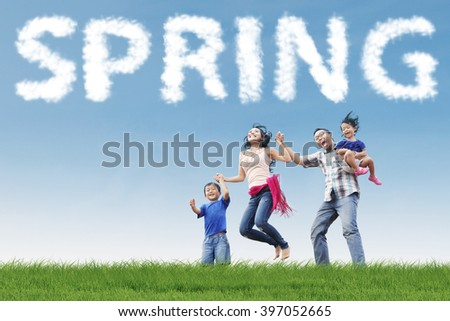 Portrait of young family leaps together on the field while holding hands under a spring cloud
