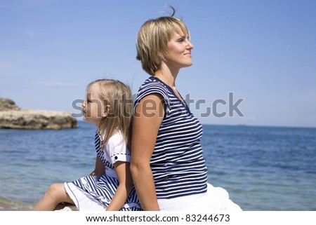 Portrait of young family, mother and daughter having fun on the beach - stock photo