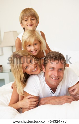 Portrait Of Young Family Relaxing In Bed Together - stock photo