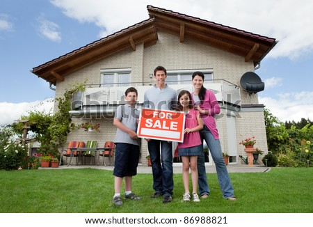 Portrait of young family selling their home holding for sale sign - stock photo