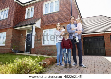 Portrait Of Young Family Standing Outside New Home - stock photo