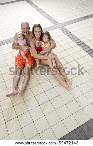 Portrait of young family with baby and toddler on pool deck tile - stock photo