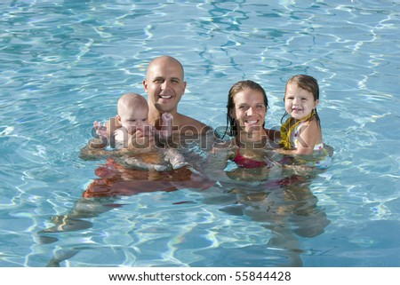 Portrait of young family with baby and toddler smiling in swimming pool - stock photo