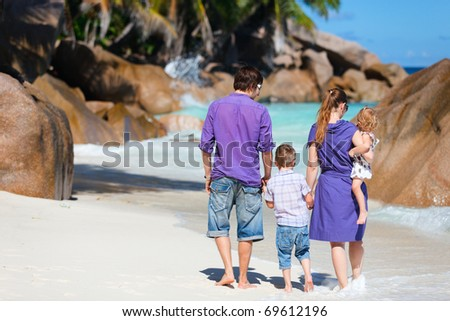 Portrait of young family with two kids walking along tropical beach - stock photo