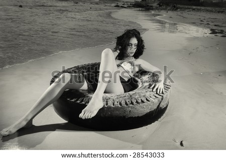 Portrait of young fashion female on the sand over tire - stock photo