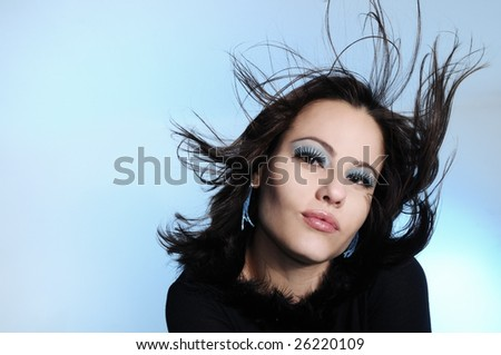 Portrait of young fashion woman with blowing hair over blue background - stock photo