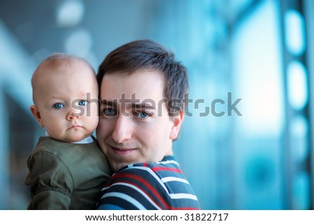 Portrait of young father and baby daughter indoors - stock photo