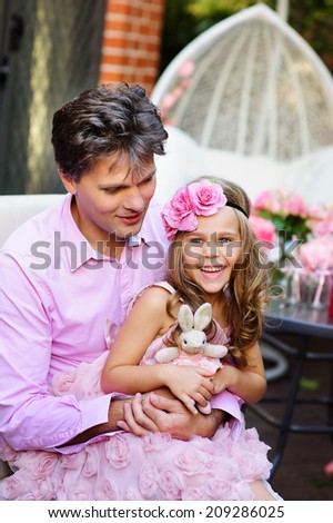 Portrait of young father and his cute daughter hug and love outdoor - stock photo