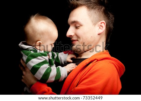portrait of young father holding its lovely six months old son, black background - stock photo