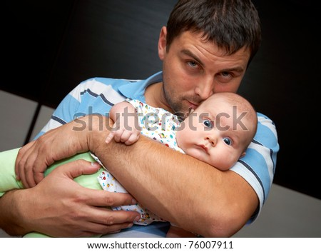 Portrait of young father is holding the baby - stock photo