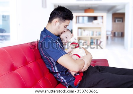 Portrait of young father sitting on the sofa while holding his baby at home