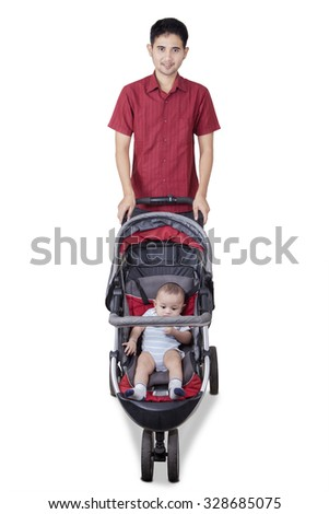 Portrait of young father standing in the studio with his baby in the stroller, isolated on white - stock photo