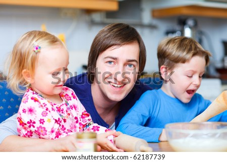 Portrait of young father with his two kids at kitchen - stock photo