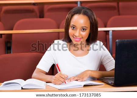 portrait of young female african college student studying in lecture hall - stock photo
