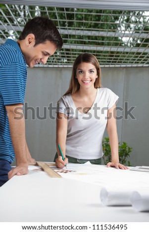 Portrait of young female architect working on blueprint with colleague standing by table
