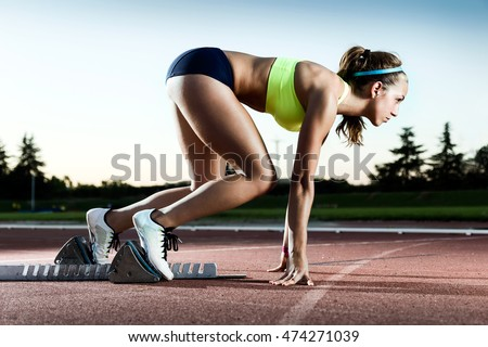 Portrait of young female athlete launching off the start line in a race.