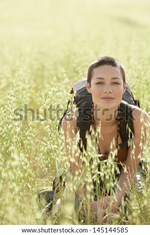 Portrait of young female backpacker crouching in field of grass - stock photo