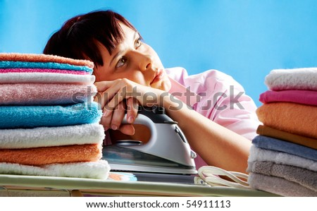 Portrait of young female between two stacks of colorful towels looking upwards