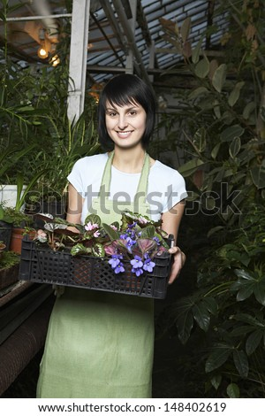 Portrait of young female botanist carrying crate full of flower plants at greenhouse - stock photo