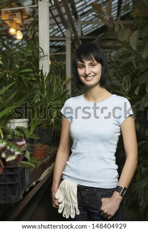 Portrait of young female botanist standing in greenhouse - stock photo