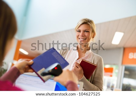 Portrait of young female college student returning book to library, with librarian scanning barcode - stock photo