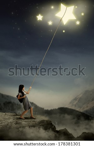 Portrait of young female college student taking stars from the sky space - stock photo