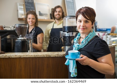 Portrait of young female customer holding coffee cup with workers in background at cafe counter - stock photo