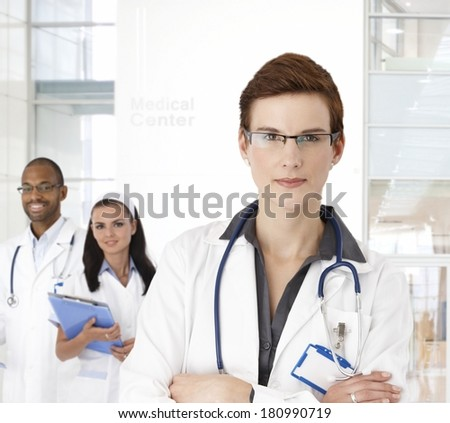 Portrait of young female doctor and team at medical center. - stock photo