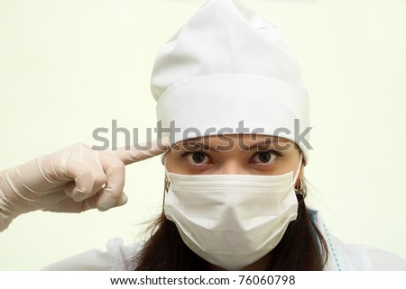 Portrait of young female doctor in mask holds a finger at a temple, showing that it is necessary to think - stock photo