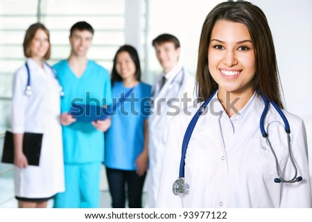Portrait of young female doctor standing in frount of his team and smiling - stock photo