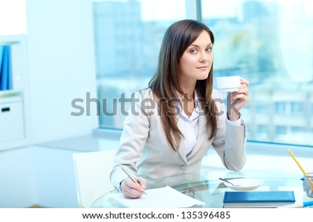 Portrait of young female drinking tea while writing proficiency test - stock photo
