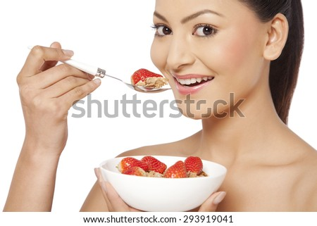 Portrait of young female eating cornflakes with strawberries - stock photo