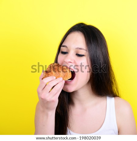 Portrait of young female eating croissant against yellow background