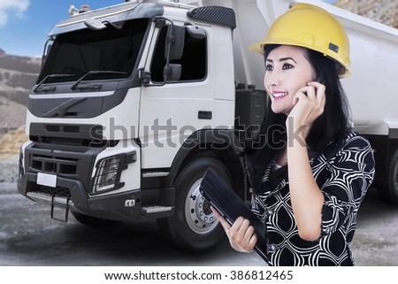 Portrait of young female engineer in builder helmet talking by phone near a big truck - stock photo