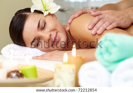 Portrait of young female enjoying the procedure of massage - stock photo