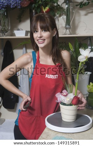 Portrait of young female florist holding clippers while standing at counter in flower shop - stock photo