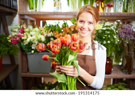 Portrait of young female florist with red tulips looking at camera - stock photo