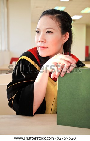Portrait of young female graduate with book in library - stock photo