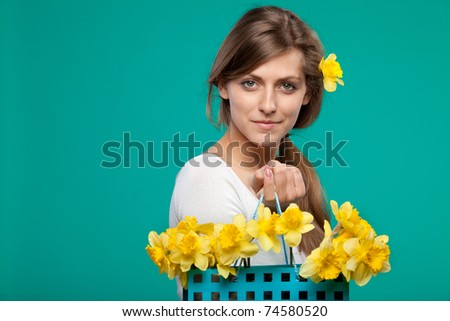 Portrait of young female holding bunch of flowers in the paper-bag isolated on turquoise background - stock photo