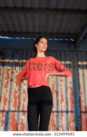 Portrait of young female jogger taking break after workout while standing against metallic wall background with copy space area for your text message or content, fit woman resting after run outdoors - stock photo