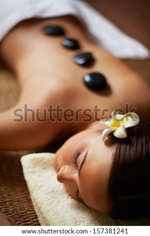 Portrait of young female lying in spa salon - stock photo