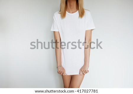 Portrait of young female model posing against home interior wearing only white blank copy space T-shirt while stretching it down. Trendy woman choosing clothes for going out to the cinema with friends - stock photo