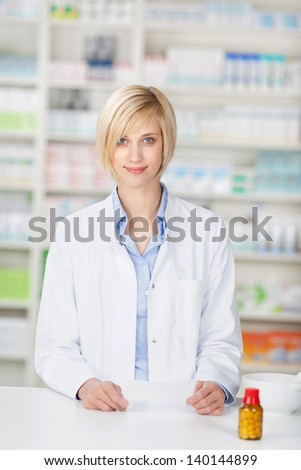 Portrait of young female pharmacist with pill bottle and prescription paper standing at pharmacy counter