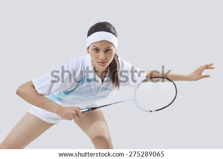 Portrait of young female player playing badminton isolated over gray background - stock photo