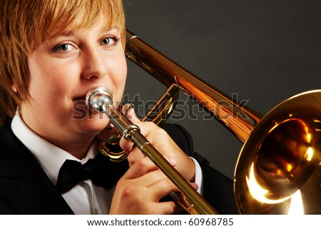 Portrait of young female playing the trombone and looking at camera - stock photo