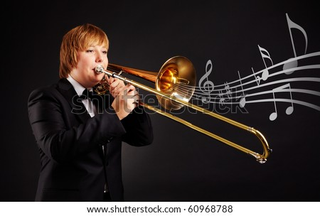 Portrait of young female playing the trombone on black background - stock photo