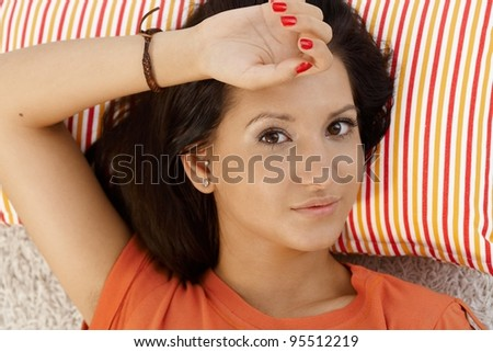 Portrait of young female resting on pillow at home, looking at camera.? - stock photo
