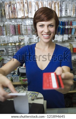 Portrait of young female sales clerk holding credit card at cash counter - stock photo